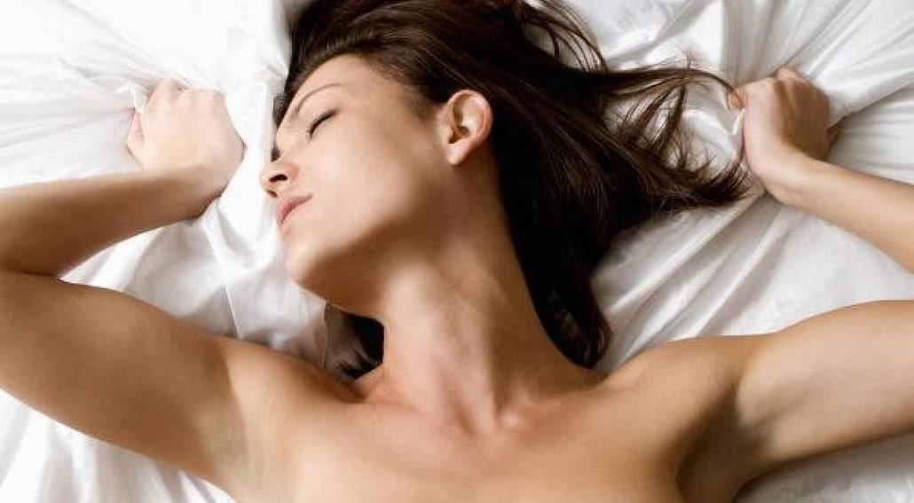 woman lying on her back with her hands above her head in ecstasy