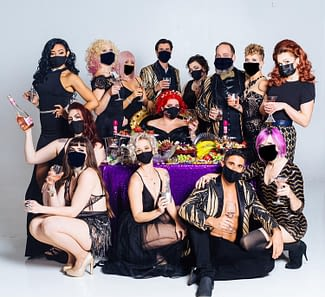 Pictured is the whole group of the Corsets & Cuties holding champagne glasses while wearing black masks.