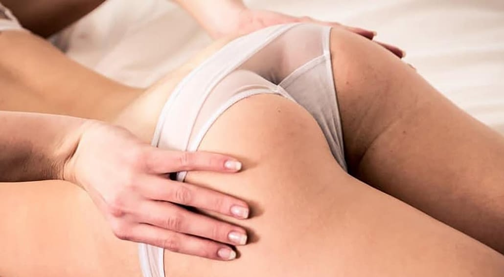 Sexy woman's butt, lying on her stomach. Her hand holding her white panties