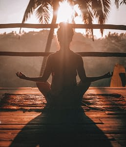 woman meditating on beach terrace