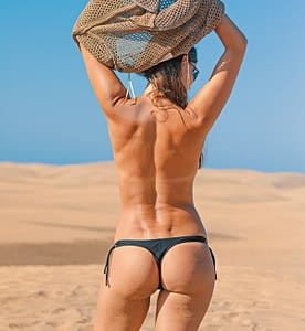 Woman on sandy beach in bikini bottom only and pulling her shirt off over her head.